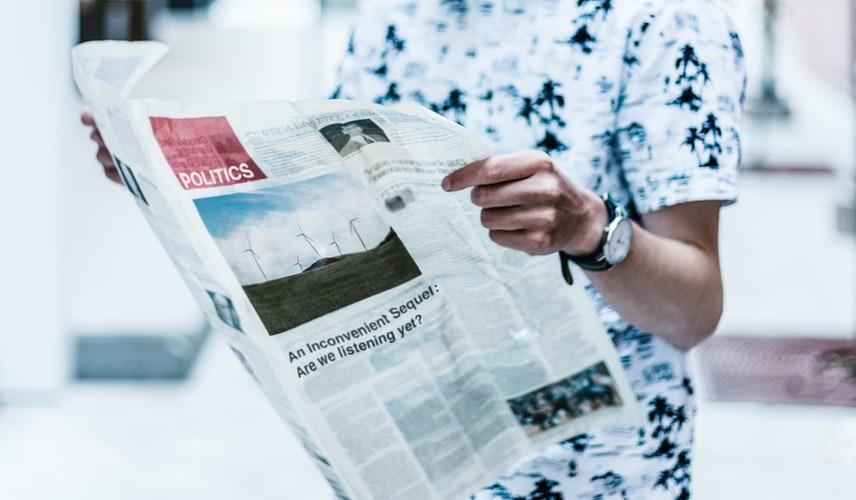 газета с политическими новостями в руках у человека